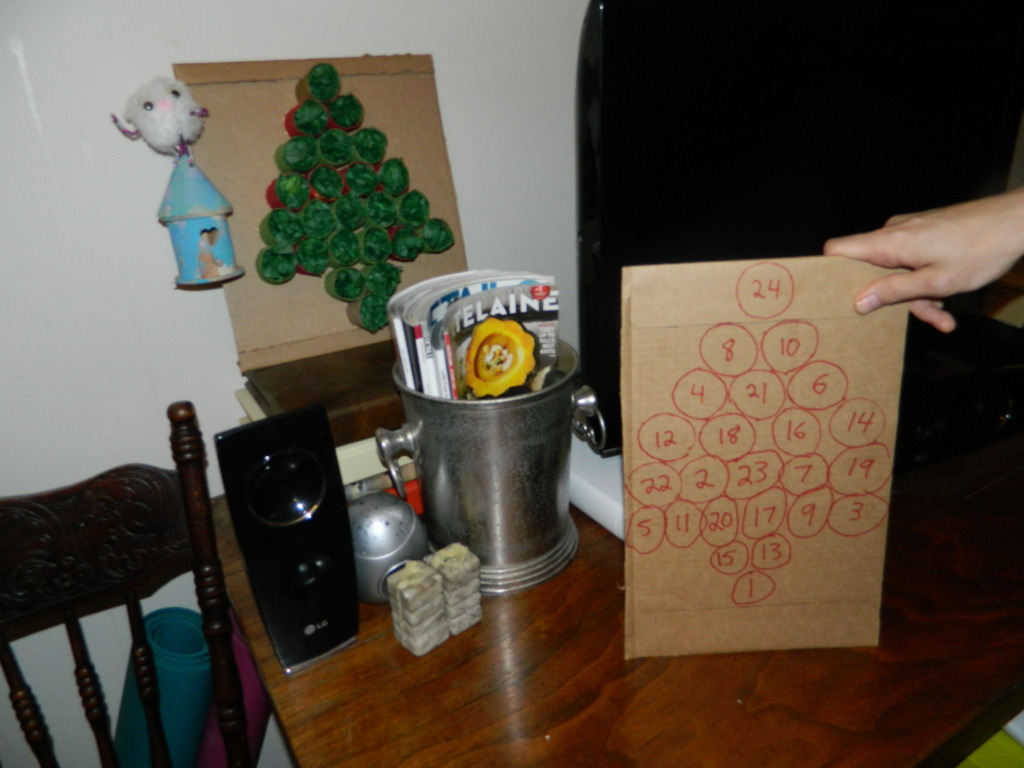 Trace circles on to another piece of cardboard or card stock. Put numbers randomly in the circles. Now your child can hunt for the number, match it to their tree advent calender and get their treat. It's really fun for them!